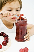 Little boy scooping jam out of jar with spoon, tart and cherries on table in front of him