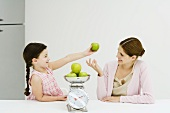 Mother and daughter weighing apples on scale, smiling at each other, girl holding up one apple