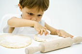 Little boy cutting out shape in dough