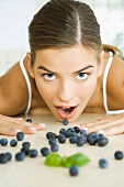 Fresh blueberries scattered across counter, young woman opening mouth to eat one