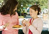 Two preteen girls eating junk food