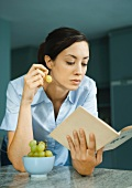 Woman reading book and eating grapes