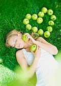 Woman lying in grass, next to apples arranged in heart shape