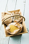Bags of lentils, millet and short grain white rice in wooden basket