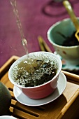 Hot water being poured and splashing over tea leaves in tea cup