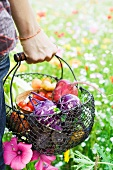 Person standing in field of wildflowers, carrying basket full of fresh produce, cropped view