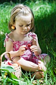 Little girl sitting on the ground holding cherries