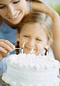 Mutter und Kind vor Geburtstagstorte beim Kerzen anzünden