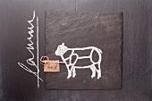 Gezeichnetes Lamm und Etikett mit Bezeichnung auf einer Schiefertafel