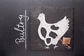 Gezeichnetes Huhn und Etikett mit englischer Bezeichnung auf einer Schiefertafel