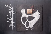 A sketch of a chicken and a written label on a chalkboard