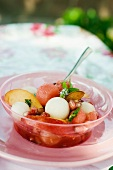 A summer fruit salad with pomegranate seeds and almonds