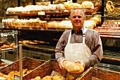Freundlicher Bäcker hält ein Brot