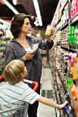Frau wählt Produkt aus Supermarktregal