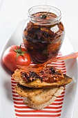 Dried tomatoes in a jar and on a slice of bread