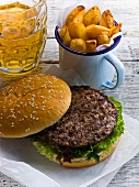 A beefburger with chips and a glass of beer