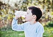 Kleiner Junge trinkt ein Glas Milch aus