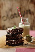 Three Stacked Marijuana Brownies; Bowl of Marijuana Buds and a Glass of Milk