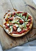 A pizza topped with king trumpet mushrooms, asparagus, goat's cheese and tomatoes