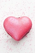 A pink, heart-shaped macaroon filled with jam