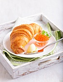A croissant with caviar and butter on a wooden tray