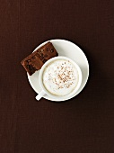 A cup of coffee with milk foam and a brownie (seen from above)