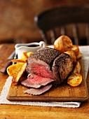Sliced roast beef on a wooden board with roast potatoes