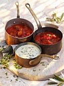 Three different pasta sauces in copper saucepans