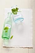 Basilikum- und Petersilieblätter und zwei Apothekerflaschen