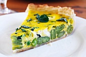 A slice of ricotta and broad bean quiche on a plate