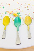 Yellow and green icing sugar on three spoons