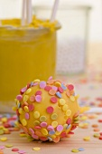 Lots of colourful sugar sprinkles on a yellow cake pop
