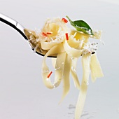 Tagliatelle, chilli, basil and grated Parmesan on a fork