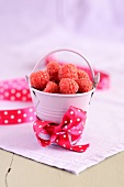 Raspberries in a small, pastel coloured bucket