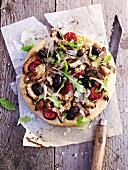 An artichoke, chorizo, black olive and rocket pizza
