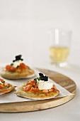 Mini pizzas topped with salmon, caviar and mozzarella