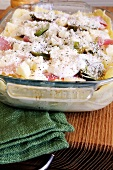Unbaked lasagne with artichokes and ham in a baking dish