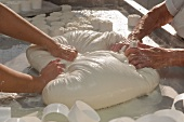 Raw milk sheep's cheese being kneaded by hand and placed in moulds (Portugal)
