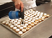 Lemon cupcakes being caramelised with a gas burner