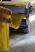 Tagliatelle being cut with a pasta machine