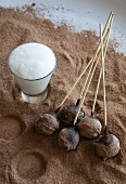 Chocolate truffles on sticks, with a glass of hot milk