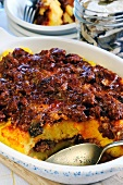 Polenta with minced meat and mushroom sauce in a baking dish