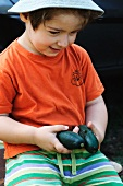 A little boy holding two cucumbers