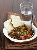 A Bowl of Lentil Stew with Flat Bread and a Glass of Water