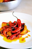 A plate of pan cooked sweet red and yellow peppers with fresh chilies and sun dried tomatoes