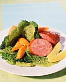 A hot pot with Savoy cabbage and sausage