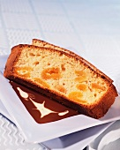 A dried apricot cake in a pool of sauce