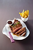A rib eye steak with balsamic sauce and chips