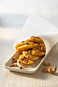 Fried banana slices with curry and nuts
