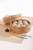 Chinesische Brötchen mit Schweinefleischfüllung im Bambuskörbchen